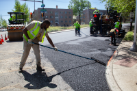 Workers from the city's street's department pave a street.