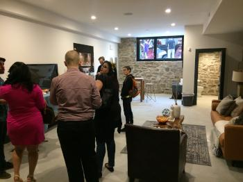 Would-be buyers, curious neighbors and members of the build team check out the Parrish House's finished basement. Through the window, a horse-drawn carriage awaits